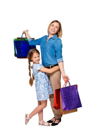 family mart: Happy  mother and daughter with shopping bags standing at studio, isolated on white background.  daughter hugging her mother