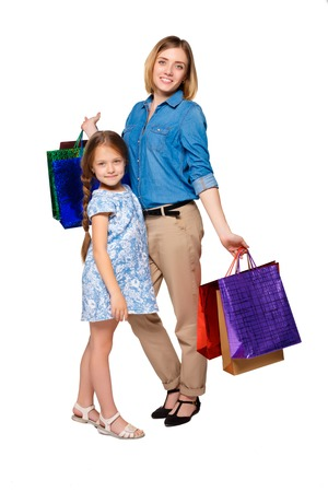 Happy  mother and daughter with shopping bags standing at studio, isolated on white background.