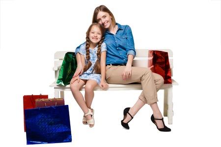 family mart: Madre e figlia felici con borse della spesa seduta a studio, isolato su sfondo bianco Archivio Fotografico