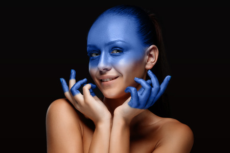 blue face: Portrait of a young woman who is posing covered with blue paint in the studio on a black background. girls hands around the face and painted blue