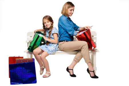considering: Happy mother and daughter with shopping bags sitting at studio, isolated on white background. they are considering purchasing and wonder
