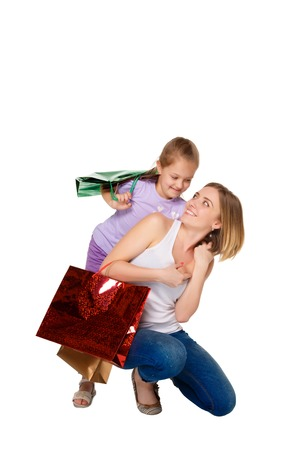 Happy  mother and daughter with shopping bags standing at studio, isolated on white background.  daughter hugging her mother