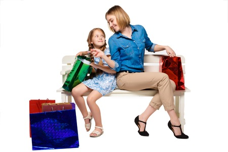 Happy mother and daughter with shopping bags sitting at studio, isolated on white background. they are considering purchasing and wonder