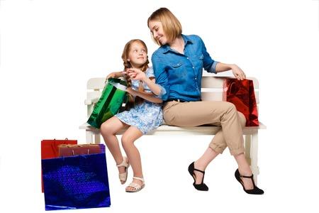 family mart: Madre e figlia felici con shopping bags, seduta in studio, isolato su sfondo bianco. essi stanno prendendo in considerazione l'acquisto e la meraviglia Archivio Fotografico