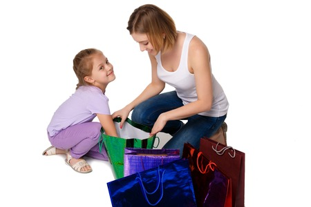 family mart: Happy  mother and daughter with shopping bags sitting at studio, isolated on white background