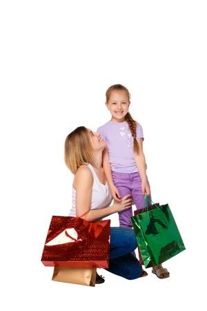 family mart: Madre e figlia felici con borse della spesa in piedi nello studio, isolato su sfondo bianco.