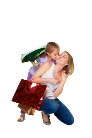 family mart: Happy  mother and daughter with shopping bags standing at studio, isolated on white background.  daughter kissing mum Stock Photo