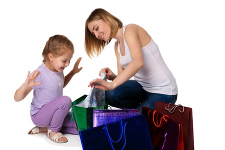 they: Happy  mother and daughter with shopping bags sitting at studio, isolated on white background. they admired considering buying