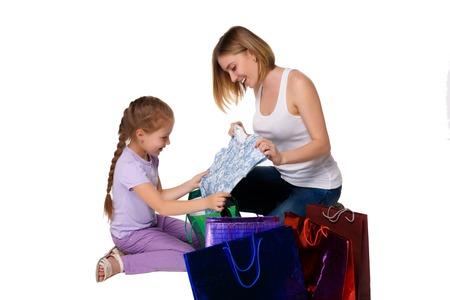 family mart: Madre e figlia felici con shopping bags, seduta in studio, isolato su sfondo bianco. ammiravano pensando di acquistare
