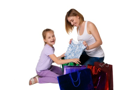 considering: Happy  mother and daughter with shopping bags sitting at studio, isolated on white background. they admired considering buying
