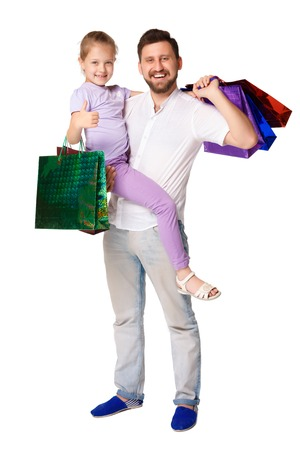 family mart: Happy father and daughter with shopping bags standing at studio, isolated on white background. father holding his daughter Stock Photo