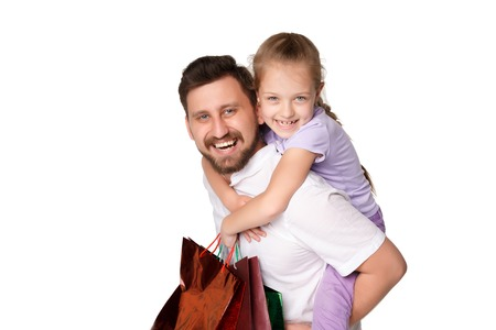 Happy father and daughter with shopping bags standing at studio, isolated on white background. father holding his daughter Stock Photo