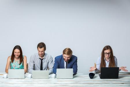 imagen: Equipo de negocios trabajando juntos en la oficina en el fondo gris claro. todos trabajando en las computadoras portátiles. copyspace
