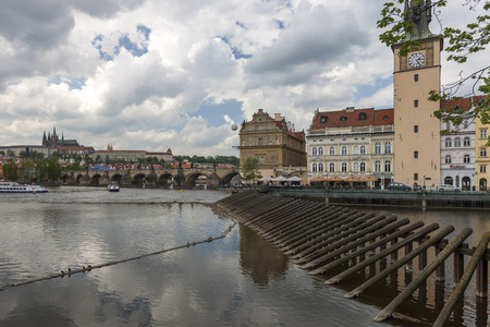 auspices: Charles Bridge is famous historic bridge that crosses Vltava river. Its construction started in 1357 under auspices of King Charles IV. View from embankment Smetana.
