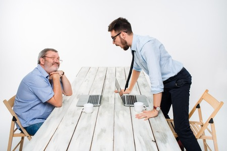 indignant: The two colleagues working together at office on light gray background. one  smiling man is satisfied, another indignant.  the concept of competition in the business