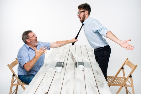 Business conflict. The two men expressing negativity while one man grabbing the necktie of her opponent on white background