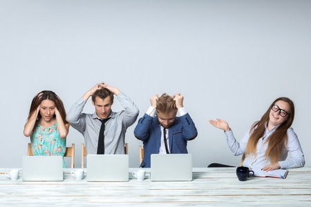 human relations: Business team working on their business project together at office on light gray background. all all grabbed his head. boss laughing. copyspace image. Stock Photo