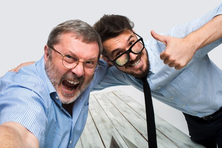 two people meeting: Two smiling colleagues taking the picture to them self sitting in the office, happy friends with glasses taking selfie with telephone camera  on white background