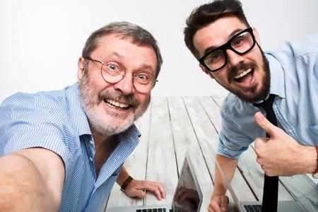 Dos colegas sonriendo tomando la foto para ellos mismo sentado en la oficina, amigos felices con gafas que toman selfie con la cámara del teléfono en el fondo blanco