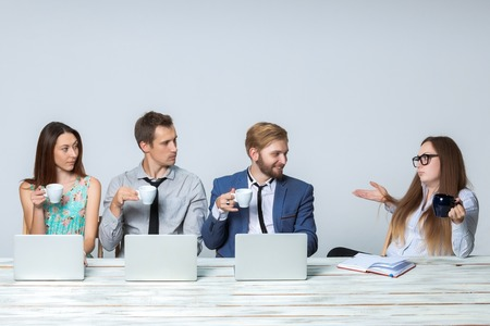밝은 회색 배경에 사무실에서 함께 그들의 비즈니스 프로젝트에서 작업하는 비즈니스 팀. 모든 커피를 마시고 보스를 찾고 있습니다. copyspace와 이미지 스톡 콘텐츠