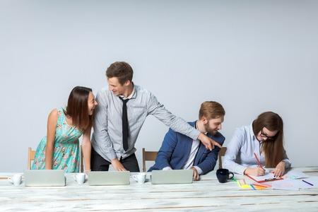 Business-Team arbeitet auf ihre Business-Projekt zusammen im Büro auf hellgrauem Hintergrund. alle lächelnd und Blick auf den Chef. der Chef ist schriftlich in einem Notebook. Copyspace Bild.