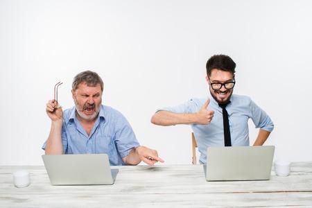 celos: Los dos colegas que trabajan juntos en la oficina en el fondo blanco. tanto los hombres est�n mirando las pantallas de ordenador. un hombre joven que consigue buenas noticias. el anciano se siente mal. concepto de competencia en los negocios y los celos