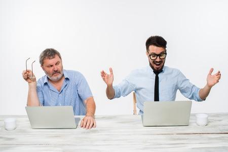 celos: Los dos colegas que trabajan juntos en la oficina en el fondo blanco. tanto los hombres están mirando las pantallas de ordenador. un hombre joven que consigue buenas noticias. el anciano se siente mal. concepto de competencia en los negocios y los celos