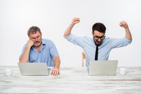 hombres trabajando: Los dos colegas que trabajan juntos en la oficina en el fondo blanco. tanto los hombres están mirando las pantallas de ordenador. un hombre joven que consigue buenas noticias. el anciano se siente mal. concepto de competencia en los negocios y los celos