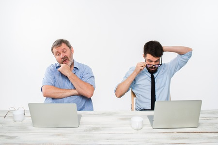 bad news: The two colleagues working together at office on white  background. both are looking at the computer screens.  concept of negative emotions and bad news Stock Photo