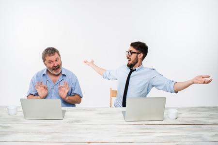 オフィスで一緒に働いている 2 人の同僚はホワイト バック グラウンドです。両方は、コンピューターの画面を見ています。両方を驚かせた。肯定的