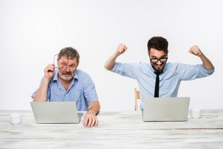 competencia: Los dos colegas que trabajan juntos en la oficina en el fondo blanco. tanto los hombres están mirando las pantallas de ordenador. un hombre joven que consigue buenas noticias. el anciano se siente mal. concepto de competencia en los negocios y los celos