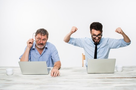 business competition: The two colleagues working together at office on white  background. both men are looking at the computer screens. a young man getting good news. the old man is upset. concept of competition in business and jealousy