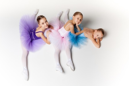 Three little ballet girls sitting  in ballet stretch in multicolored tutu and pointe shoes together on white background