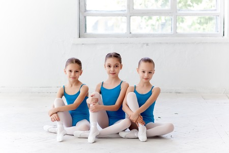 DAnce background: Three little ballet girls sitting in pointe shoes together on white background in ballet studio