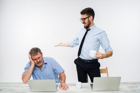 celos: Los dos colegas que trabajan juntos en la oficina en el fondo blanco. El joven que consigue buenas noticias. el anciano se siente mal. concepto de competencia en los negocios y los celos