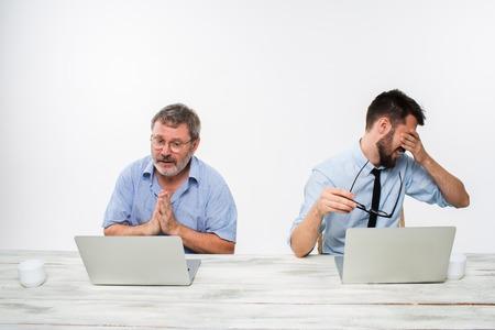 celos: Los dos colegas que trabajan juntos en la oficina en el fondo blanco. El anciano que consigue buenas noticias. el joven se siente mal. concepto de competencia en los negocios y los celos