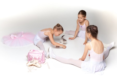little girl swimsuit: Three little ballet girls sitting in white swimsuit and pointe shoes together with cat on white background in ballet studio Stock Photo
