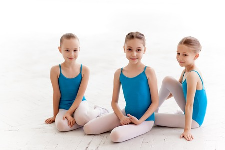 Tres niñas de ballet que se sientan en traje de baño azul y zapatos de punta juntos en el fondo blanco en el estudio de ballet Foto de archivo - 42834044