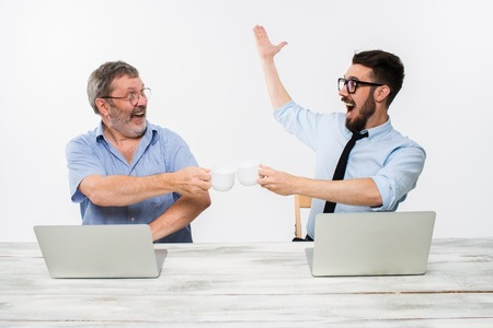 getting together: The two colleagues working together at office on white  background. both happy men are getting good news. concept of  success in business Stock Photo