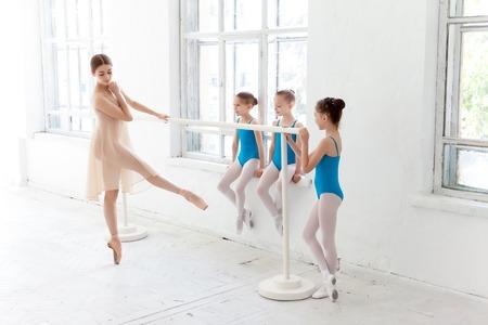 T�nzerIn: Drei kleine Ballerinas mit pers�nlichen Ballettlehrer im Tanzstudio. klassische Ballettt�nzerin als Lehrer posiert auf einem Bein am Ballettstange auf einem wei�en Hintergrund Lizenzfreie Bilder