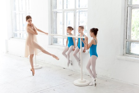 leotard: Three little ballerinas with personal ballet teacher in dance studio. classic ballet dancer  as teacher posing on one leg at ballet barre on a white background