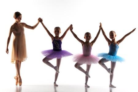 Las siluetas de las pequeñas bailarinas con el maestro de ballet personal en el estudio de danza posando sobre un fondo blanco Foto de archivo