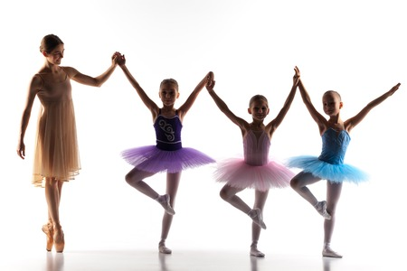 ballerina costume: The silhouettes of little ballerinas with personal ballet teacher in dance studio posing on a white background