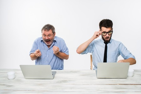 stockbroker: The two colleagues working together at office on white  background. The old man getting good news. the young man is upset. concept of competition in business and jealousy