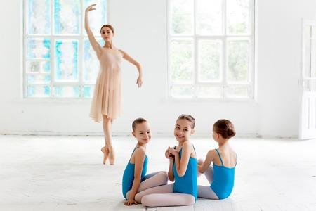 Drie kleine ballerina's met persoonlijke ballet leraar in dansstudio. klassiek balletdanser als leraar die zich voordeed op een witte achtergrond