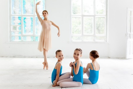 danza clasica: Tres pequeñas bailarinas con el maestro de ballet personal en el estudio de danza. bailarina de ballet clásico como profesor posando sobre un fondo blanco Foto de archivo