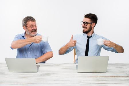 흰색 배경에 사무실에서 함께 작동하는 두 동료. 모두 행복 사람들이 좋은 소식을 얻고있다. 사업 성공의 개념. 그들은 기쁨과의 clinking 컵