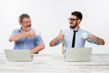 Les deux collègues qui travaillent ensemble au bureau sur fond blanc. deux hommes heureux obtiennent de bonnes nouvelles. concept de la réussite en affaires. ils se réjouissent et tintement tasses