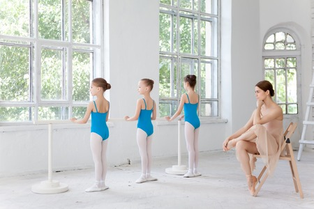 Three little ballerinas with personal classic ballet teacher in dance studio posing at ballet barre on a white background