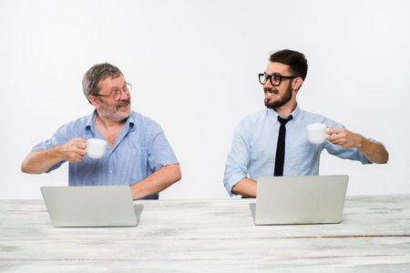getting together: The two colleagues working together at office on white  background. both happy men are getting good news. concept of  success in business. they rejoicing and clinking cups